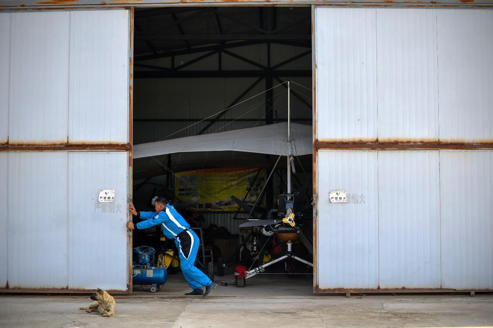 在银川市贺兰县,刘亦兵拉开机库大门,做飞行前准备工作(6月21日摄)。